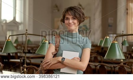 Portrait Of Beautiful Student Girl Happily Looking In Camera Standing With Backpack And Textbook In