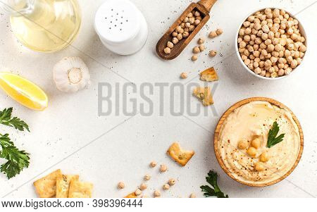 Flatlay Hummus In A Wooden Plate And Raw Chickpeas In A Bowl. Dishes Of Chickpeas, A Vegetarian Dish
