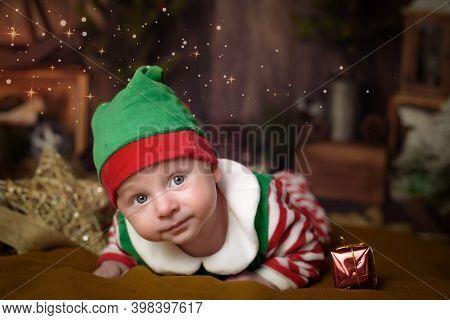 Happy Baby Elf Helper Of Santa In Costume Santa Claus With Gift At Christmas Tree