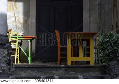 Multicolored Wooden Tables And Chairs Outdoors. Suggestive Place To Have Lunch.
