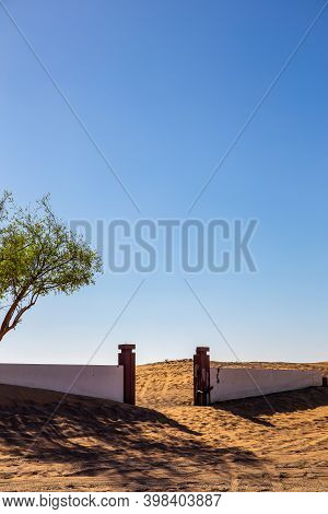 Al Madam Ghost Village, Abandoned Courtyard And Brick Fence With Entry Gate Buried In Sand In Sharja