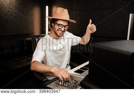Young Stylish Music Producer Happily Showing Thumb Up Gesture Composing New Song In Sound Recording