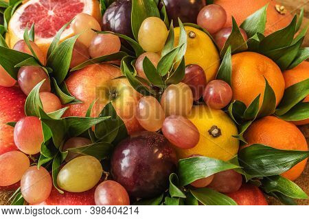 Fruit Bouquet Of Apples, Lemons, Plums, Grapes, Tangerines, Grapefruit And Green Leaves Close Up