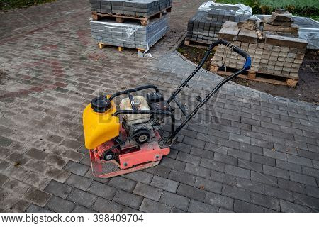 Vibrating Plate Compactor Machine At A Construction Site. Equipment For Soil Thrombosis. Compaction
