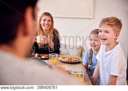 Family Sitting Around Table At Home In Pyjamas Enjoying Brunch Together