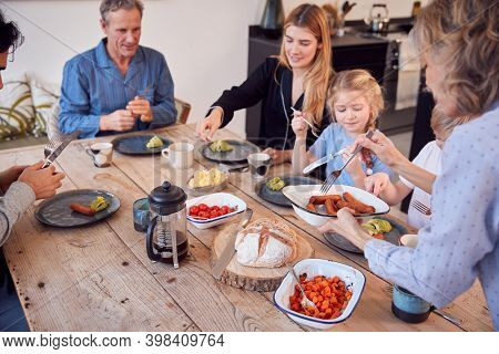 Multi-Generation Family Sitting Around Table At Home In Pyjamas Enjoying Brunch Together