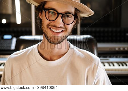 Young Stylish Sound Producer Working In Modern Recording Studio. Handsome Musician Happily Looking I