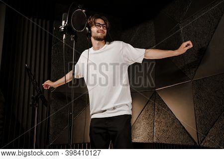 Young Attractive Male Singer In Headphones Dancing During Record New Song In Modern Studio. Young Mu