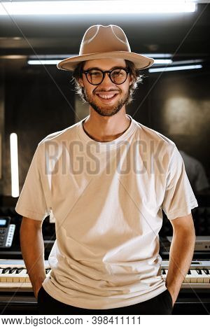 Handsome Confident Guy In Hat Happily Looking In Camera In Studio. Young Stylish Sound Producer Work