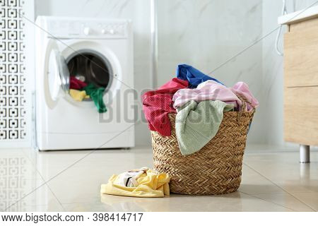 Wicker Laundry Basket With Different Clothes On Floor Near Washing Machine In Bathroom. Space For Te
