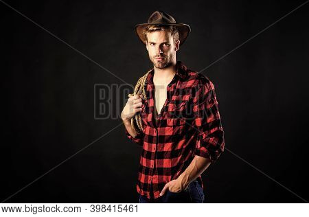 Heating Up Wild West. Wild West Rodeo. Man In Hat Black Background. Man Checkered Shirt On Ranch. Vi