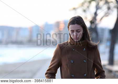 Front View Portrait Of A Sad Woman Walking Alone Towards Camera Looking Down On The Beach In Winter