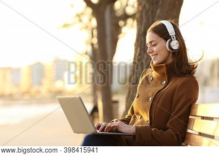 Happy Woman Wearing Headphones Using Laptop In Winter Sitting On A Bench On The Beach