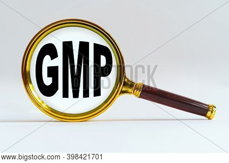 Finance And Economics Concept. Magnifier On A White Background, Inside The Text Is Written - Gmp