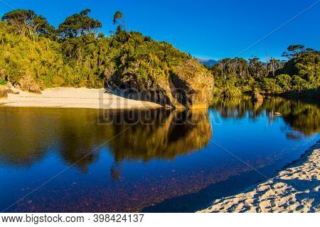 Travel to the ends of the world. New Zealand, South Island. The road to Knight's Point Lookout is an unforgettable majestic landscape. Picturesque magic reflections of overgrown shores