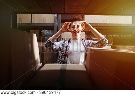 Female Warehouse Worker Making Cello Tape Glasses, Captured Through Shelf
