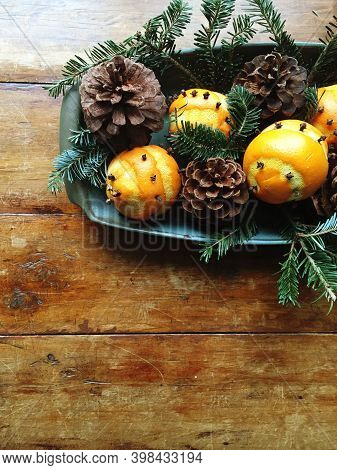 Clove-studded Orange Pomanders, Pinecones And Evergreens In A Tray.