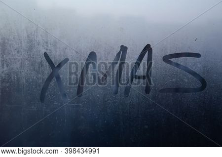 Xmas Drawn On Misted Window On The Background Of The City. Inscription Xmas With Finger On Misted Gl