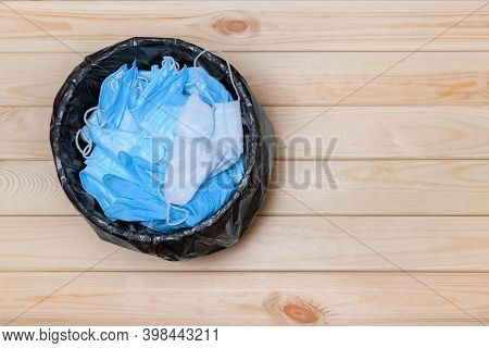 Trash Bin With Masks On Floor, Top View. Used Masks. Disposable Masks In Trash Bucket. Medical Mask