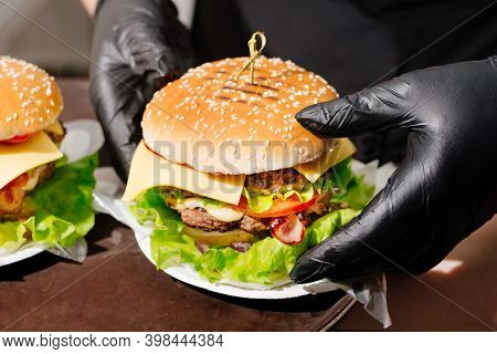 Big Double Burger. Gloved Hands Picking Up A Double Burger From A Tray In A Diner