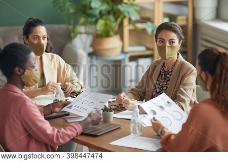 High Angle View At Multi-ethnic Group Of Young Businesswomen Wearing Masks During Meeting In Office,