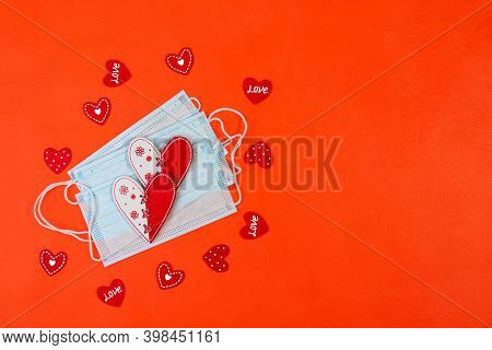 Medical Face Masks With Red Hearts On A Red Background. Safe Valentine's Day Concept. Top View, Copy