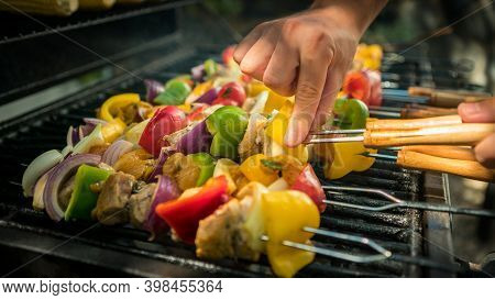 Hand Of Man With Bbq Grill. Cook A Delicious Skewers On Grilled Meat In A House
