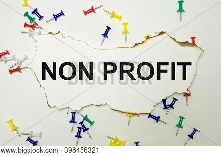 The Word Non Profit Written On A White Background Next To A Paper Clip