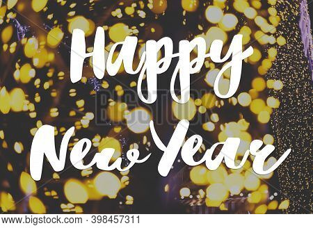 Happy New Year Greeting Card. Happy New Year Text Handwritten On Illumination With Warm Golden Light