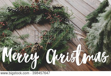 Merry Christmas Greeting Card. Merry Christmas Text Handwritten On Modern Christmas Wreath With Berr