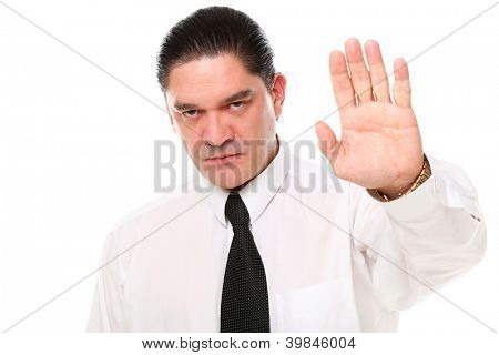 Serious mid aged businessman showing stop gesture over a white background