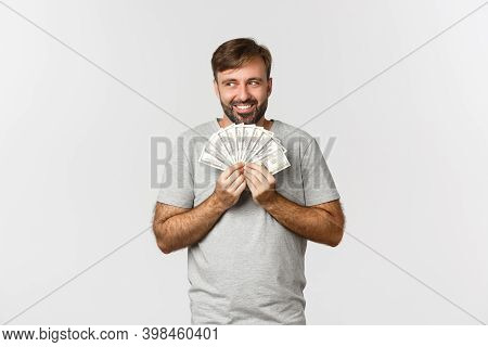 Greedy Smiling Greedy Man With Beard, Thinking About Shopping, Holding Money And Looking At Upper Le
