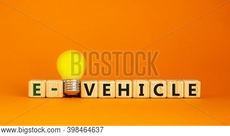 E-vehicle Symbol. Wooden Cubes With Word 'e-vehicle'. Yellow Light Bulb. Beautiful Orange Background