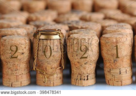 Closeup of a large group of Champagne corks, with the date 2021 that fill the frame. Selective focus on the front row. One cork has the metal cage. Horizontal format.