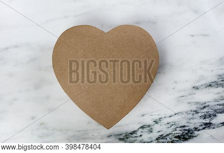 A Large Cardboard Heart Giftbox For Happy Valentines Day  On A Marble Stone Background