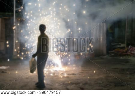 Blurred Image Of Young Man Lighting Up Fire Crackers At Night,event Of Kali Puja, A Hindu Indian Fes