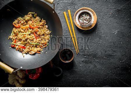 Wok Rice With , Soy Sauce And Bell Pepper. On Black Rustic Background