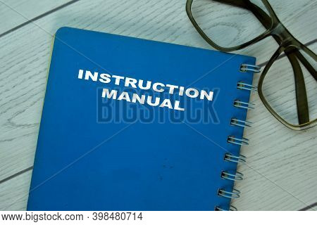 The Book Of Instruction Manual On Office Desk.