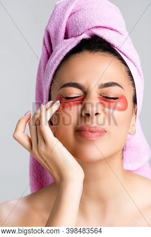 Beautiful Woman With Towel On Hair And Hydrogel Eye Patches On Face Closing Eyes Isolated On Grey