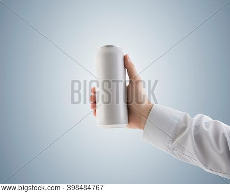 Man holding white blank aluminum can with beverage with clipping path