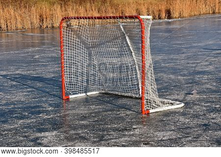 A Hockey Goalie Box Is Left On The Frozen Ice Of A Slough With Reeds And Dried Grass In The Backgrou