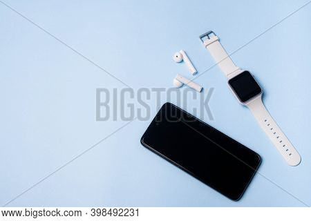 The Layout Of The Watch And The Phone On A Blue Background. Appliances And Electronics. Modern Gadge