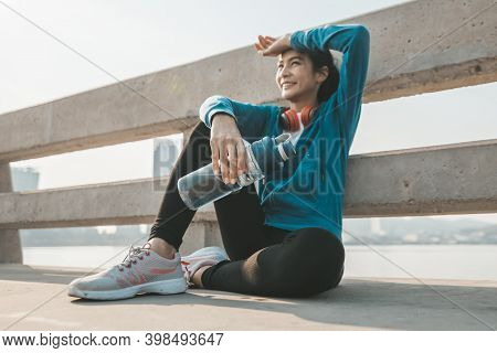 Woman Athlete Thirsty Takes A Break. She Sitting And Hold Water Bottle After Running.