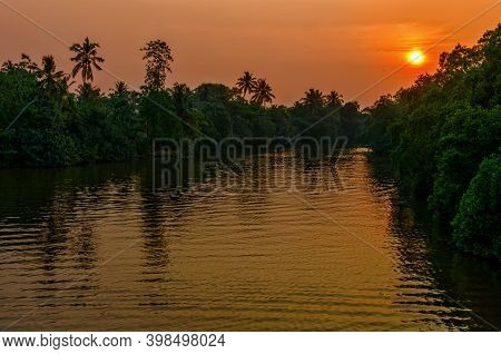 Sunset Above The River In Jungle With Trees Along The Banks.  Forest River Sunset Scene.