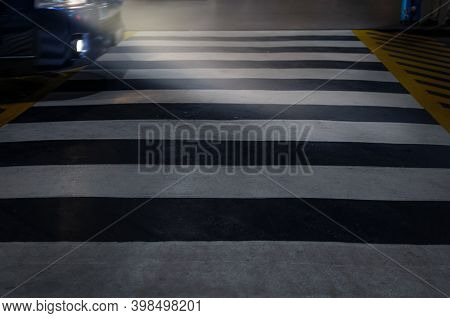 Car With Glowing Headlights Drives At Night Through A Pedestrian Crossing.  Defocused Photo With Blu