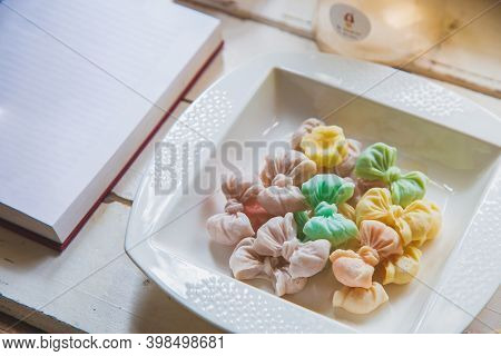 High Angle Views Allure Thai Candy In A White Disk On A White Wooden Table With An Open Book.