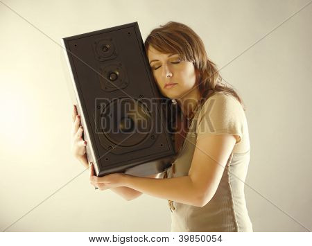 Young beautiful woman with closed eyes holding big wooden speaker and listening music