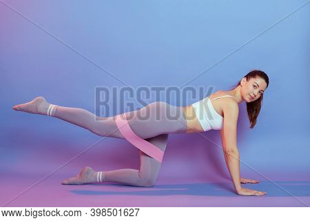 Happy Young Sportswoman Doing Exercises, Back Straightening, Leg Up, Using Rubber Resistance Ban. Lo