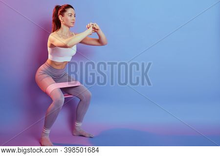 Photo Of Fitness Girl In Stylish Sportswear Squats With Rubber Band On Background Of Blue And Rose W