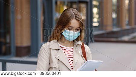 Close Up Portrait Of Caucasian Teen Schoolgirl Standing Outdoor At Schoolyard In Mask And Reading Fr